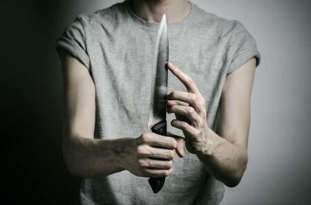 Murder and Halloween theme: a man holding a knife on a gray background studio