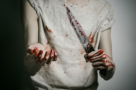 Blood and Halloween theme: man holding a bloody knife in his hand, a bloody murderer studio