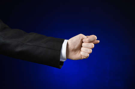 fico: Businessman and gesture topic: a man in a black suit and white shirt showing hand gesture on an isolated dark blue background