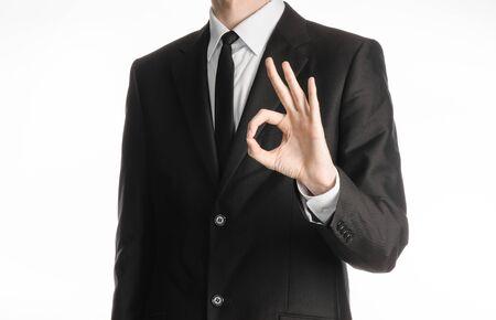 El hombre de negocios y el gesto tema: un hombre en un traje negro con una corbata que muestra gesto de mano aceptable en un fondo blanco aislado