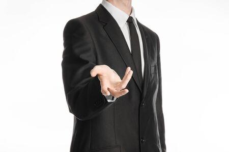 adentro y afuera: El hombre de negocios y el gesto tema: un hombre con un traje negro y corbata tiende la mano aisladas sobre un fondo blanco