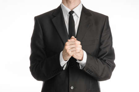 plead: Businessman and gesture topic: a man in a black suit with a tie folded his hands in front of him and praying, meditating businessman isolated on a white background Stock Photo