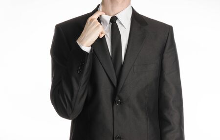 narrowly: Businessman and gesture topic: a man in a black suit and tie holding a hand to his shirt collar isolated on a white background
