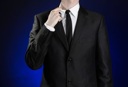 narrowly: Businessman and gesture topic: a man in a black suit and white shirt correcting a jacket and tie on a dark blue background in studio