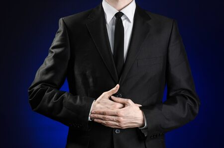 penniless: Businessman and gesture topic: a man in a black suit and a white shirt holding hands on the sick belly on a dark blue background in studio