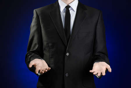 indebtedness: Businessman and gesture topic: a man in a black suit and white shirt showing gestures with hands on a dark blue background in studio