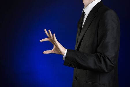 pinch: Businessman and gesture topic: a man in a black suit and white shirt shows a hand pinch on a dark blue background in studio Stock Photo