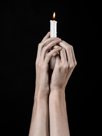 death candle: hands holding a candle, a candle is lit, black background, solitude, warmth, in the dark, Hands death, hands witch Stock Photo