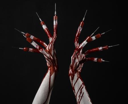 mano insanguinata con la siringa sulle dita, dita dei piedi siringhe, siringhe mano, orribile mano insanguinata, tema halloween, zombie medico, sfondo nero, isolato