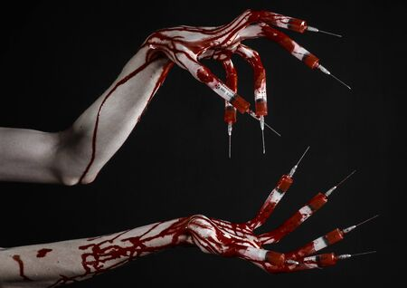 black toes: Bloody hand with syringe on the fingers, toes syringes, hand syringes, horrible bloody hand, halloween theme, zombie doctor, black background, isolated