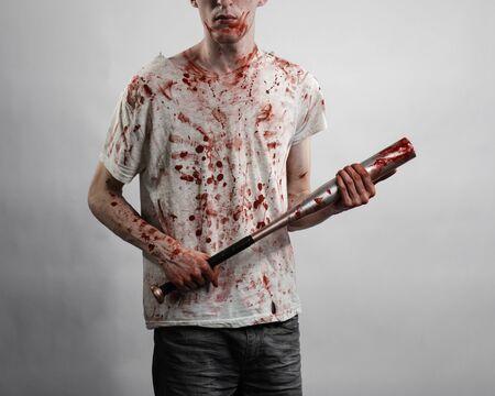 tema sangrienta: El individuo en una camiseta ensangrentada con un bate con sangre sobre un fondo blanco