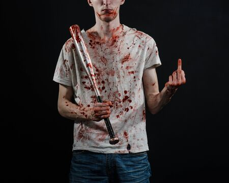 Bloody topic: The guy in a bloody T-shirt holding a bloody bat on a black background Stock Photo