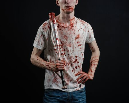 youth crime: Bloody topic: The guy in a bloody T-shirt holding a bloody bat on a black background Stock Photo