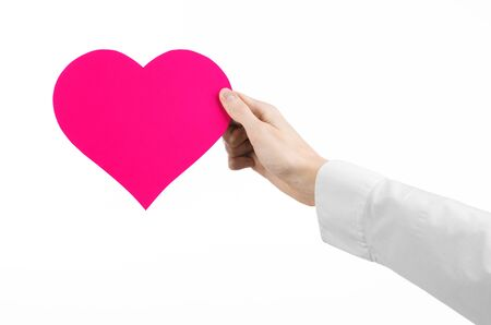 heart symbol: Heart Disease and Health Topic: hand doctor in a white shirt holding a card in the form of a pink heart isolated on a white background in studio