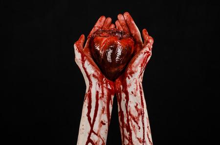 Sang et Halloween thème: la main sanglante terrible tenir déchiré saignement coeur humain isolé sur fond noir en studio Banque d'images