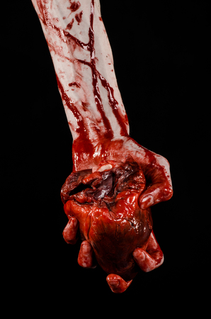 Blood and Halloween theme: terrible bloody hand hold torn bleeding human heart isolated on black background in studio Reklamní fotografie