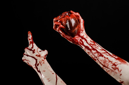 walking corpse: Blood and Halloween theme: terrible bloody hand hold torn bleeding human heart isolated on black background in studio Stock Photo