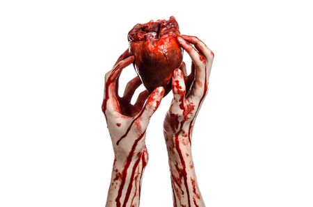 carnage: Blood and Halloween theme: terrible bloody hand hold torn bleeding human heart isolated on white background in studio