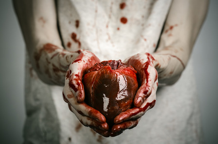 walking corpse: Bloody Halloween theme: crazy killer keeps bloody hands torn bloody human heart and experiencing depression and pain