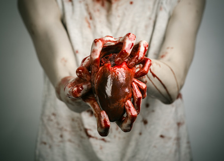 carnage: Bloody Halloween theme: crazy killer keeps bloody hands torn bloody human heart and experiencing depression and pain