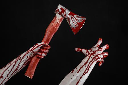 血まみれのハロウィーンのテーマ: スタジオで黒の背景に分離された血の肉屋の斧を持っている血の手