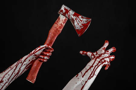 Bloody Halloween theme: bloody hand holding a bloody butchers ax isolated on black background in studio