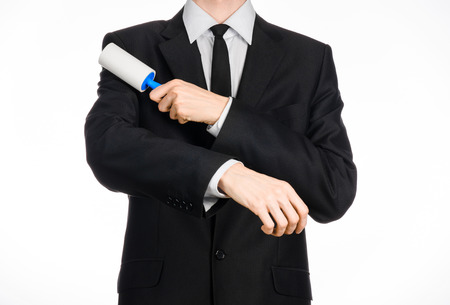 dry suit: Dry cleaning and business theme: a man in a black suit holding a blue sticky brush for cleaning clothes and furniture from dust isolated on white background