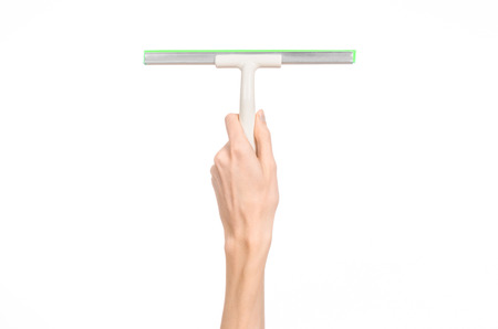Household cleaning and washing windows theme: man's hand holding a green scraper windows isolated on a white background