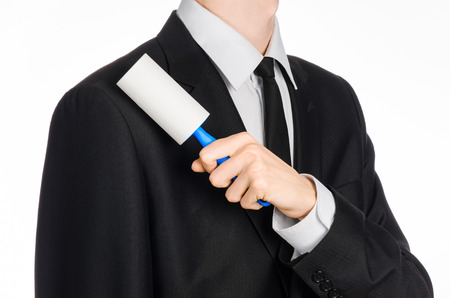 Dry cleaning and business theme: a man in a black suit holding a blue sticky brush for cleaning clothes and furniture from dust isolated on white background