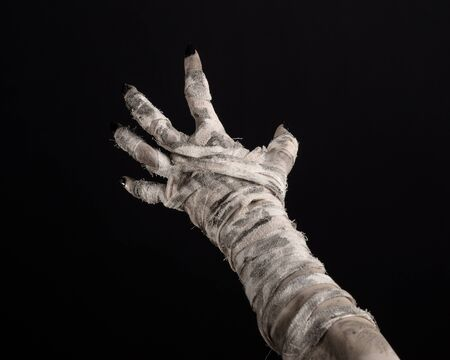 mummified: Halloween theme: terrible old mummy hands on a black background Stock Photo