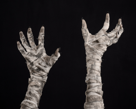 walking corpse: Halloween theme: terrible old mummy hands on a black background Stock Photo