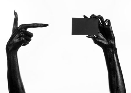 Halloween and gothic theme: The Black Hand of death holding a blank black card on white isolated background in the studio, the walking dead