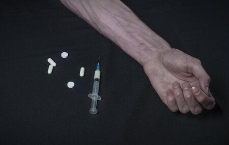 narc: Addiction theme: hand addict with syringe with drugs on a dark background studio