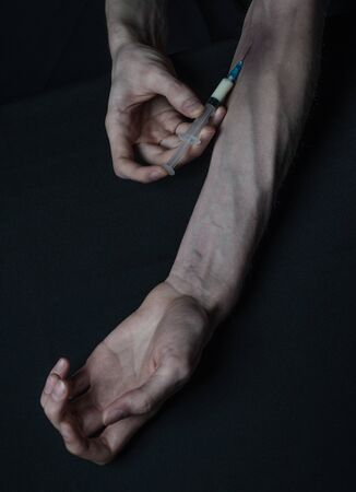 Addiction theme: hand addict with syringe with drugs on a dark background studio