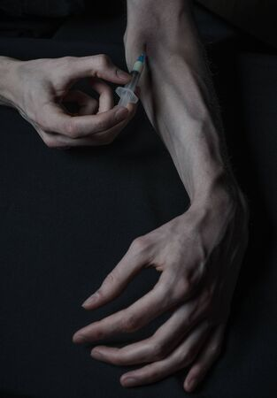 narc: Addiction theme: hand addict with syringe with drugs on a dark background studio