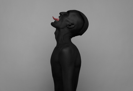 dramatic characters: Gothic and Halloween theme: a man with black skin is isolated on a gray background in the studio, the Black Death body art studio