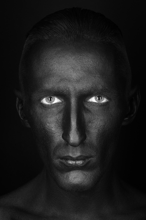 dramatic characters: Gothic and Halloween theme: a man with black skin is isolated on a black background in the studio, the Black Death