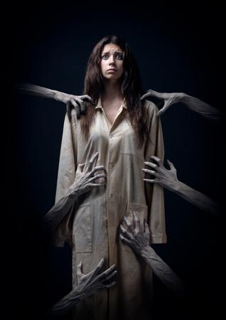 meisje in een vuile gewaad, met de hand van de dood, nachtmerries, slapeloosheid, een geesteszieke vrouw, halloween thema, griezelige droom, de handen van de demon, de handen van de duivel in de rook, horrorfilm scene met een vrouw, angst in de studio