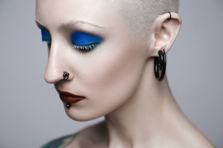 Makeup and beauty topic: punk girl with blue eyes and red lips on gray background