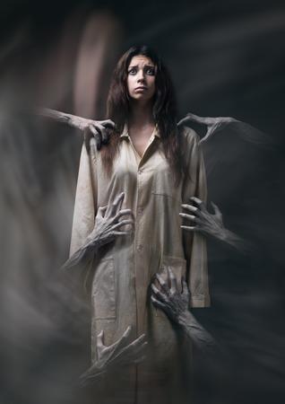 chica con una túnica sucia, mano de la muerte, pesadillas, insomnio, una mujer enferma mental, tema de halloween, espeluznante sueño, las manos del demonio, las manos del diablo en el humo, escena de película de terror con una chica, el miedo en el estudio