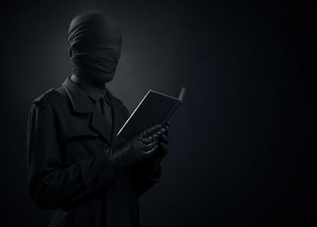 Black Art, a man in a black suit, tied head, loneliness, depression in studio