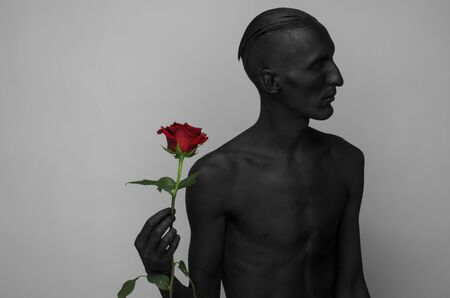 corpse flower: Gothic and Halloween theme: a man with black skin holding a red rose, black death isolated on a gray background Stock Photo