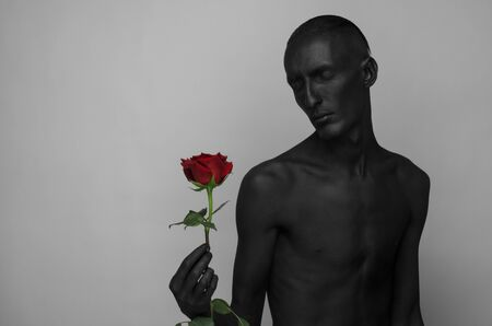 dramatic characters: Gothic and Halloween theme: a man with black skin holding a red rose, black death isolated on a gray background Stock Photo