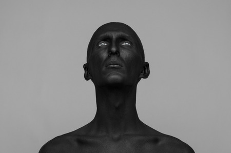 dramatic characters: Gothic and Halloween theme: a man with black skin is isolated on a gray background in the studio, the Black Death Stock Photo