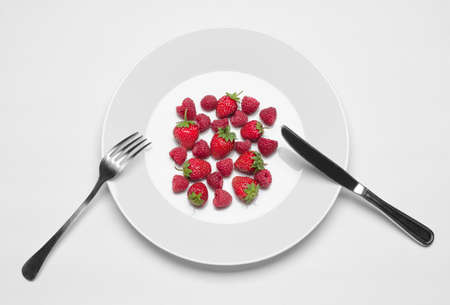 Healthy eating in the restaurant and diet Topic: white plate with strawberries and raspberries and a metal knife and fork lying on a white table in the studio isolated top view