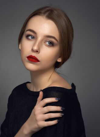 Portrait of a beautiful young girl with red lips and black clothes on a dark background in the studio shot Standard-Bild