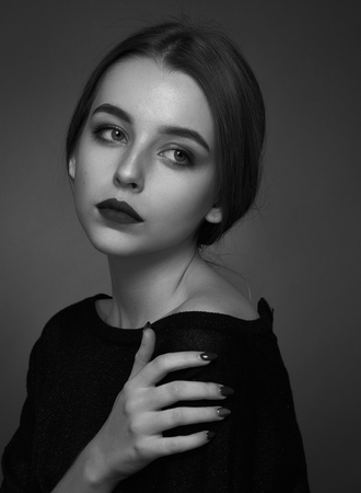 Dramatic black and white portrait of a beautiful girl on a dark background in the studio Standard-Bild
