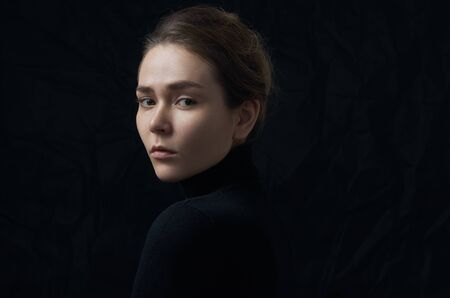 Dramatic portrait of a young beautiful girl with freckles in a black turtleneck on black background in studio shot