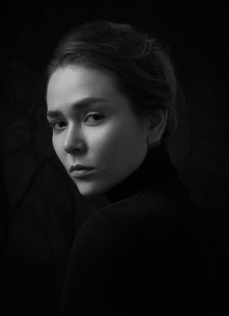 Dramatic black and white portrait of young beautiful girl with freckles in a black turtleneck on black background in studio shot