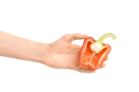 Healthy eating and diet Topic: Human hand holding a half of red pepper isolated on a white background in the studio shot